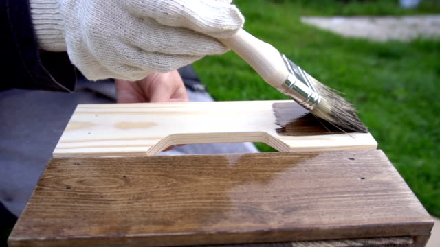 Woman painting wooden box with a brush video