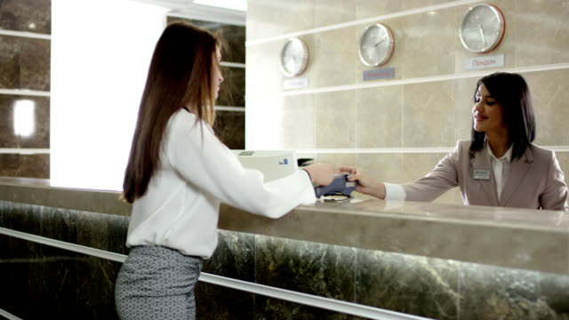 woman paying for appartament in the hotel at the reception and get a key video