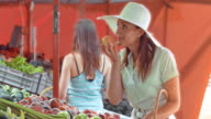 Woman paying for apples she picked out on market stall video