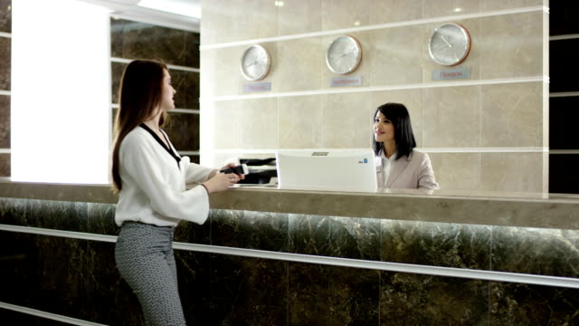 woman paying for room in the hotel at the reception video