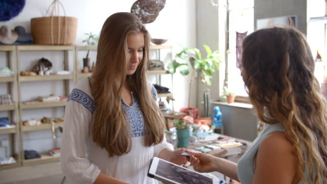 Woman paying shop assistant with credit card in a boutique video