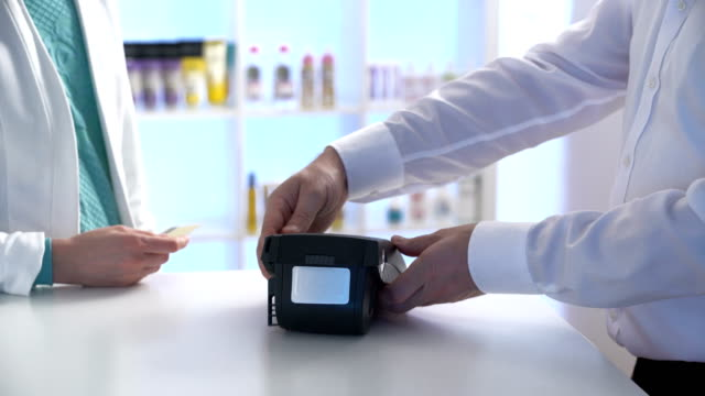 Woman paying through smartphone using NFC technology. Close up video