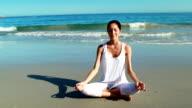 Woman performing yoga at beach video