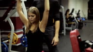Woman performs a bench press dumbbells over your head, under guidance of a coach video