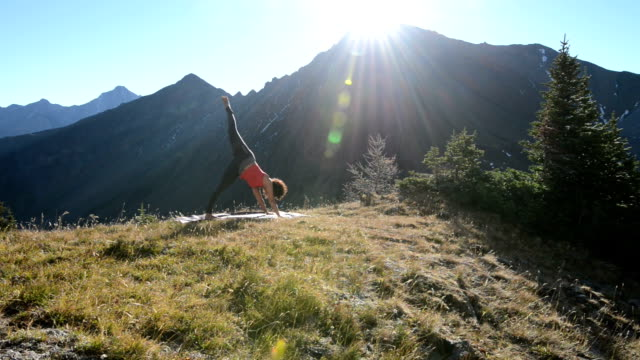Woman performs yoga exercises in mountain meadow video