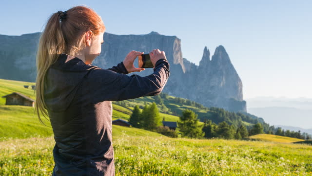 Woman photographing mountain scenery video