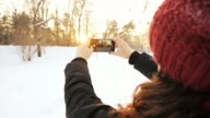 Woman photographing the sunset in winter time. video