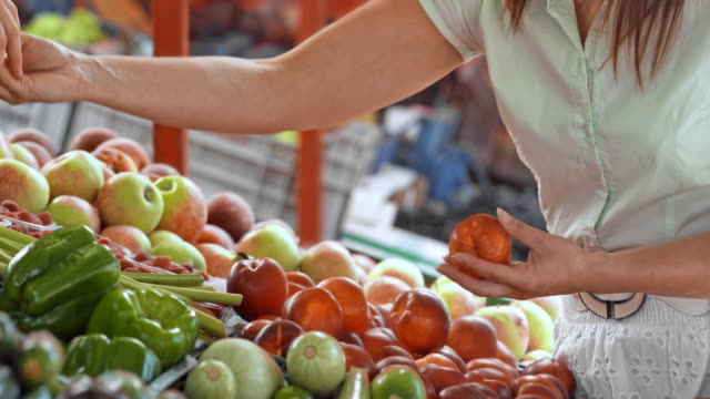 Woman picking out produce at a market stall and paying video