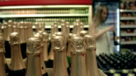 Woman picking up a bottle of wine in supermarket video