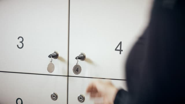 Woman placing bag in a locker in gym video