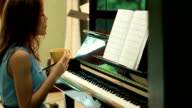 Woman plaing piano and drink coffee video