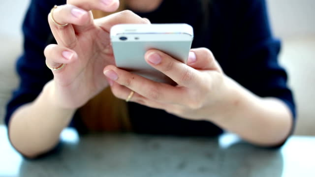 Woman play smartphone at coffee shop cafe video