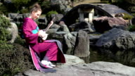 HD: Woman playing shamisen in Japanese garden (video) video