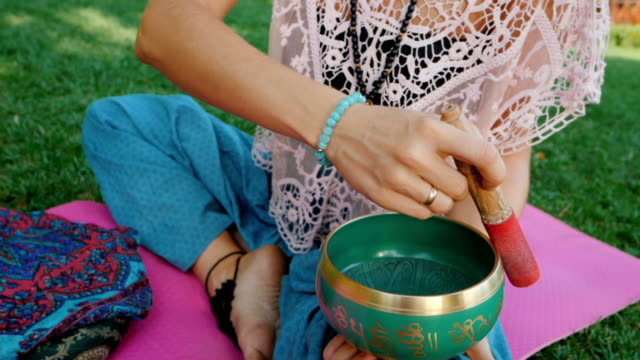 Woman playing singing bowl while sitting on pink yoga mat in park at summer. Vintage tonned. Beautiful girl with mala beads meditating on green grass. Slow motion video