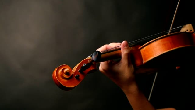 Woman playing violin over dark background video
