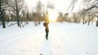 Woman playing with snow in the park at sunset. video