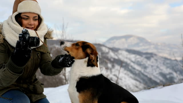 Woman playing with the dog in fresh snow video