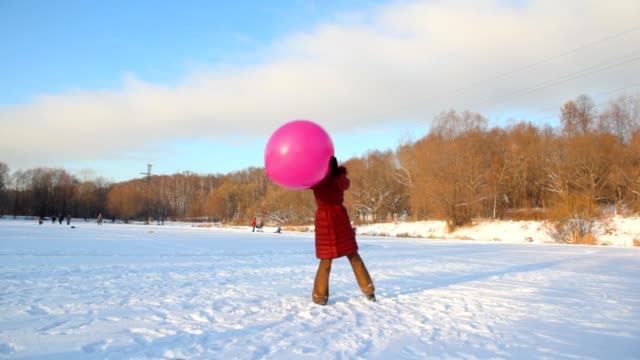 Woman plays with big air-balloon in wintry snowfield video