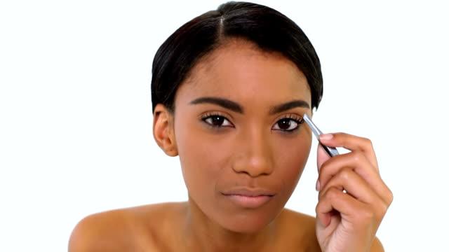 Woman plucking eyebrow with tweezers video