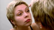 Woman plucks and pulls her eyebrows out at mirror video