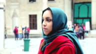 Woman portrait wearing an headscarf in front of a mosque video