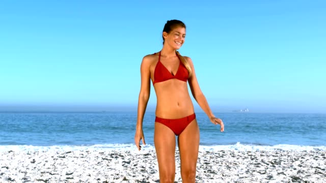 Woman posing and revolving on the beach video