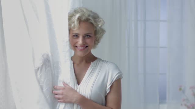 Woman posing with curtain video