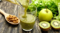 Woman pouring a green detox juice from blender to a jar, at home wearing sport clothes video