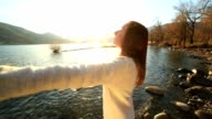 Woman practicing breathing exercise at sunrise video