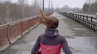 Woman practicing running on bridge video