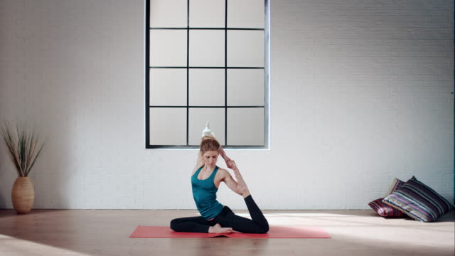 Woman practicing yoga in gym (half pigeon pose) video