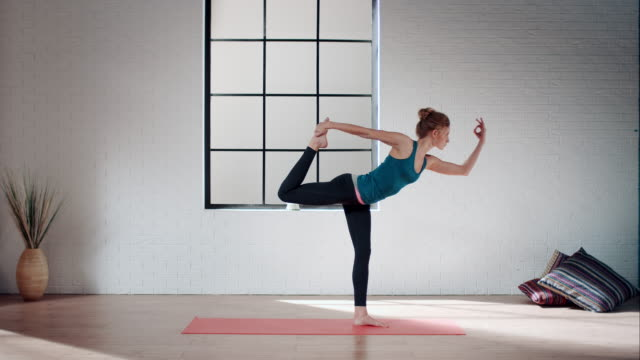 Woman practicing yoga in gym (lord of the dance pose) video