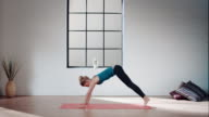Woman practicing yoga in gym (downward facing dog pose) video