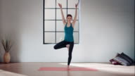 Woman practicing yoga in gym (tree pose) video