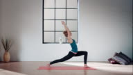 Woman practicing yoga in gym (moon pose) video