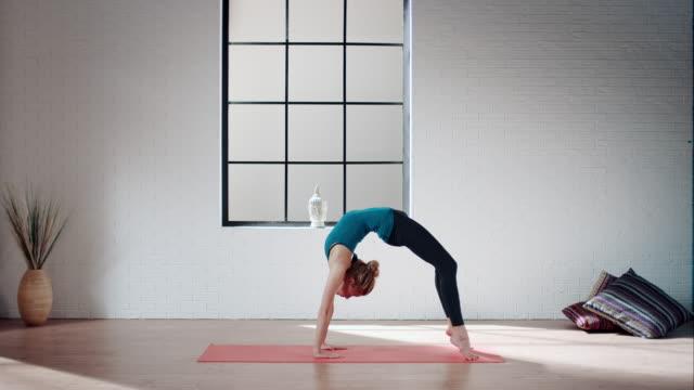 Woman practicing yoga in gym (bridge pose variation) video