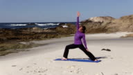 Woman Practicing Yoga on the Beach video