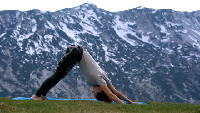 woman practicing yoga outdoors video