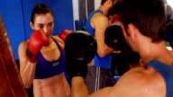 Woman practising boxing with trainer video