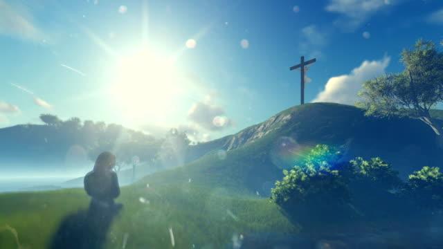 Woman praying at Jesus cross against beautiful morning sun, panning video