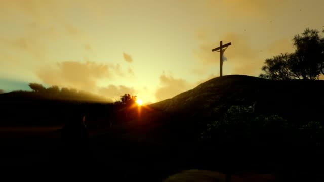 Woman praying at Jesus cross against beautiful sunrise, panning video