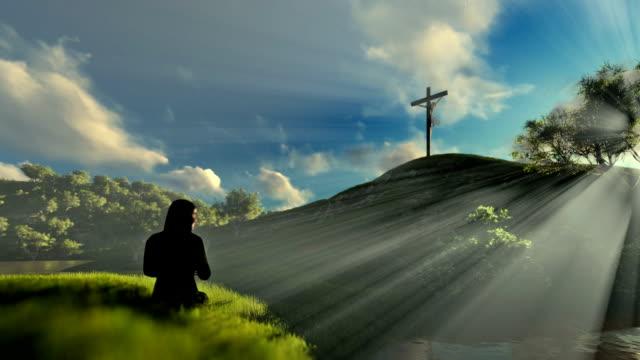 Woman praying at Jesus cross over beautiful morning sun rays video