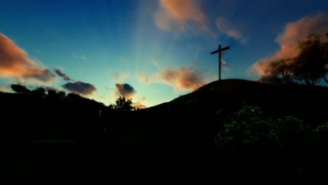 Woman praying at Jesus cross over beautiful sunrise video
