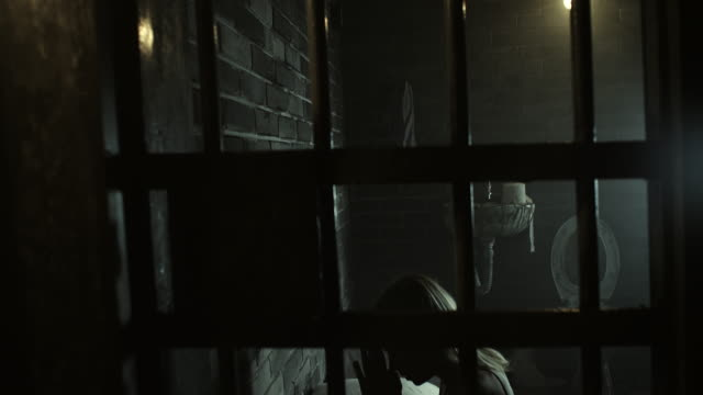 Woman praying at prison cell video