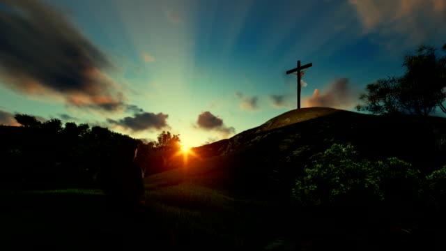 Woman praying over Jesus cross against beautiful timelapse sunrise video