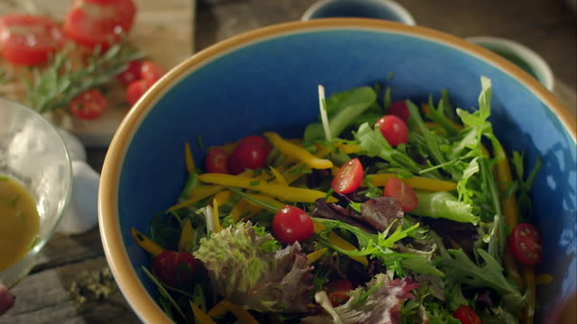 Woman preparing salad for dinner video