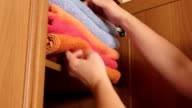 Woman pulling out stack of colorful fluffy bath towels from the shelf of wardrobe video