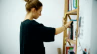 Woman pulls a book from the bookshelf video
