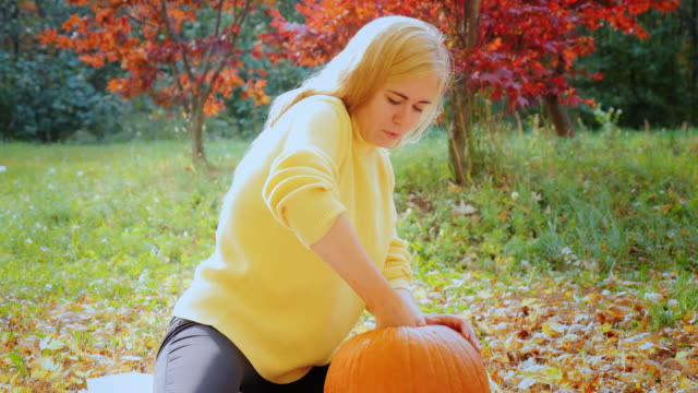 A woman pulls out the insides of the pumpkin. Preparing for Halloween video