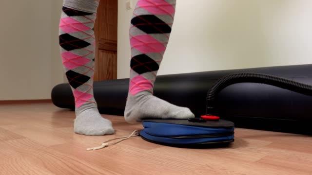 Woman pumping air into the air mattress video